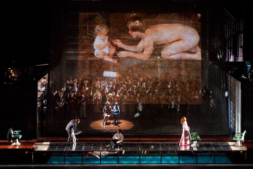 Al principio de la ópera se pueden ver grandes proyecciones audiovisioales y filmaciones en tiempo real concebidas por Denis Guéguin. Foto: © Bastille création. Cortesía: Teatro Real.