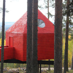Blue Cone es un cabaña roja encaramada a un árbol a la que se accede a través de un puente. Foto: © Treehotel.
